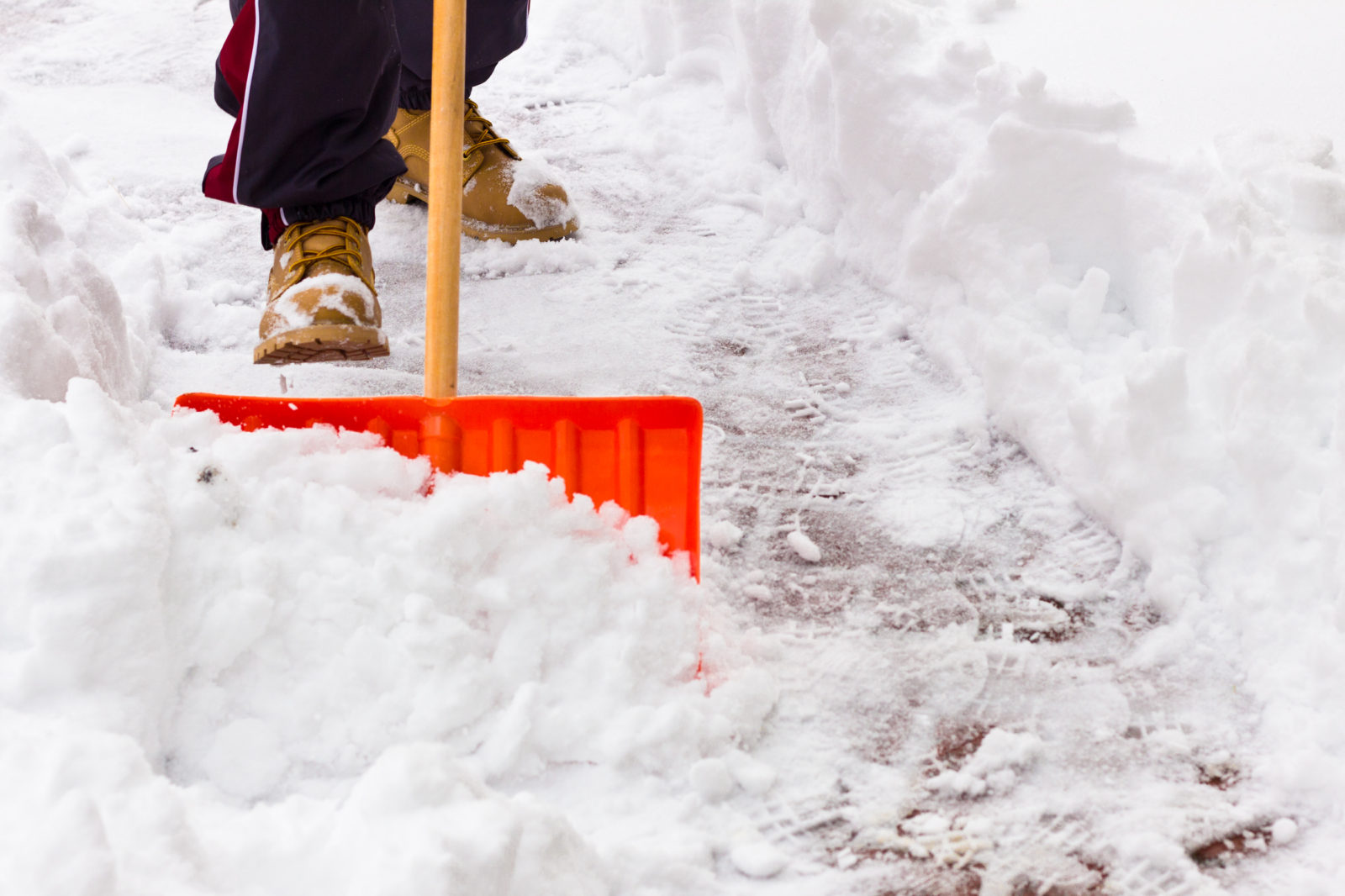 A picture of someone shoveling snow from a sidewalk, to illustrate a winter storm alert post. LCA