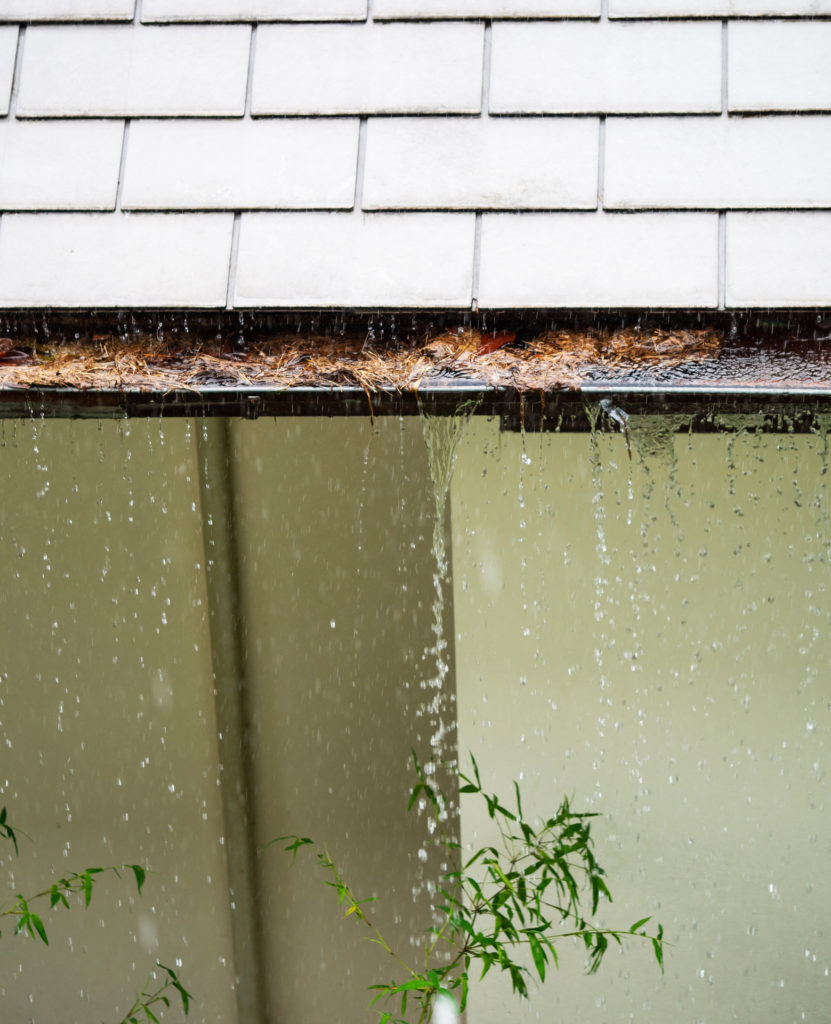 An image showing rainwater flooding a clogged gutter, which can cause water problems such as flooding.
