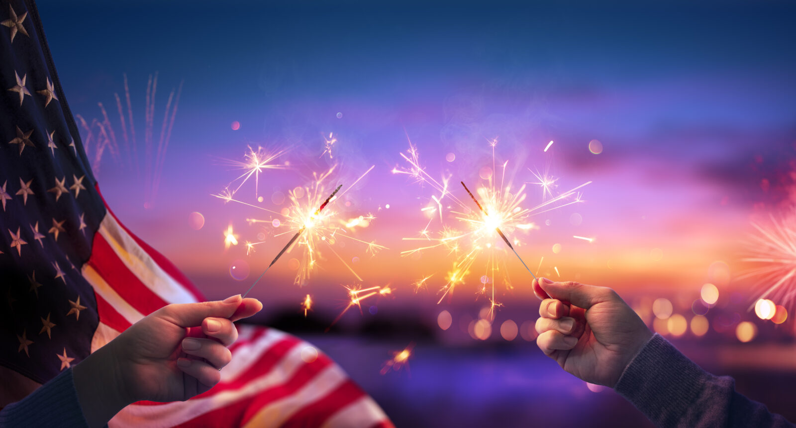 Hands holding sparklers against a background of fireworks, for a blog post from LCA on fireworks safety.