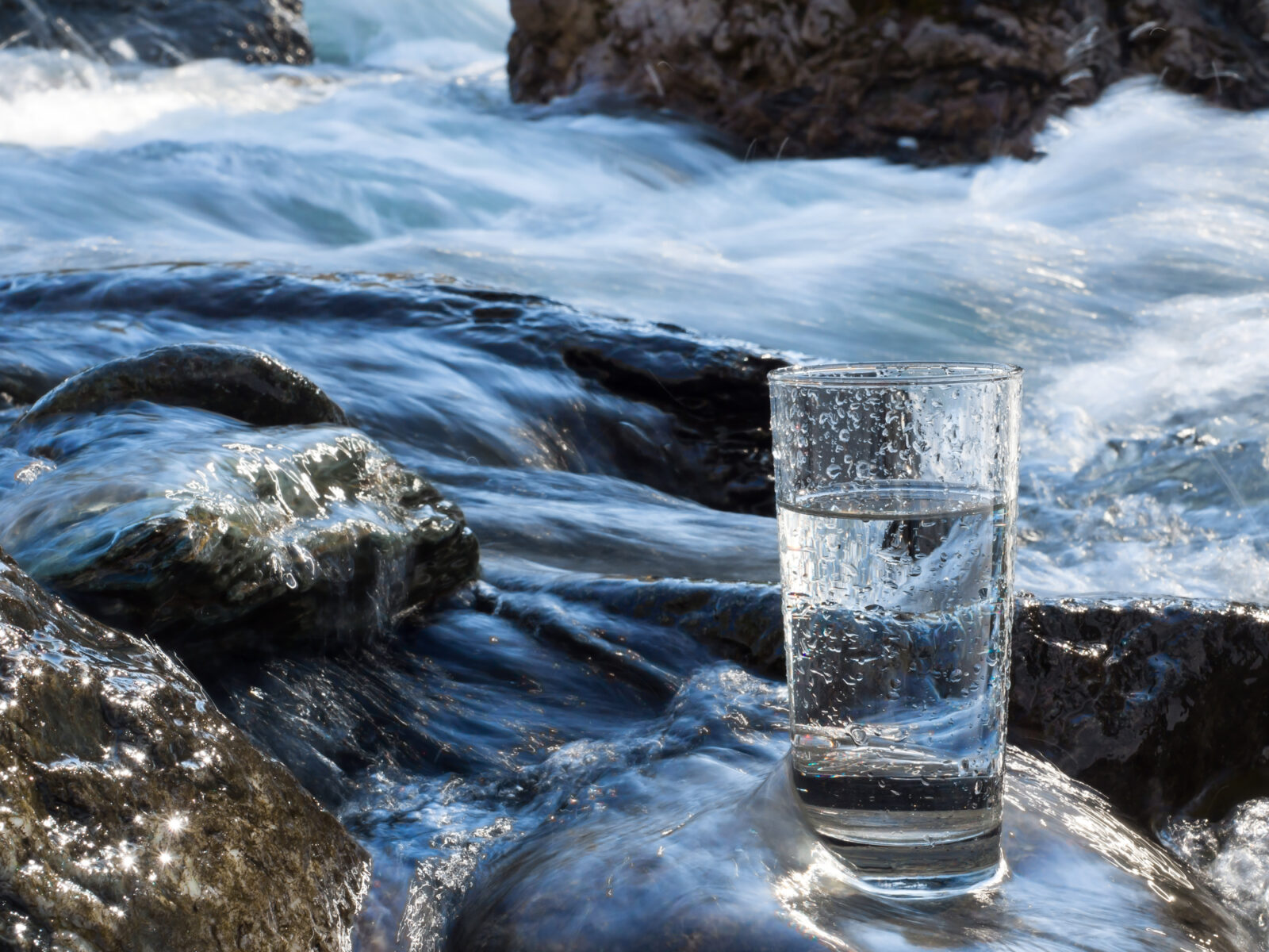 A picture of a drinking glass in a stream for a post on Source Water Protection Week.